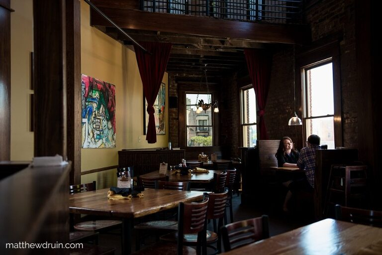 Engaged couple smiling at each other while sitting at table by window in Terminal Brewhouse during Chattanooga engagement session