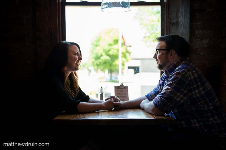 Engaged couple talking and holding hands in Terminal Brewhouse during Chattanooga engagement session