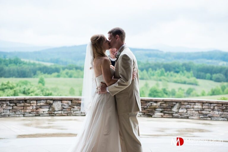 Bride and groom first kiss at ceremony at Chattooga Belle Farm wedding