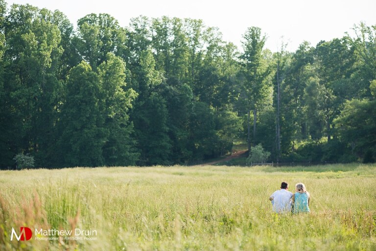 Wide shot of engaged couple sitting in field at romantic sunset engagement
