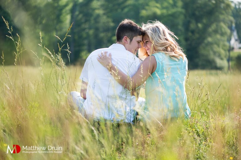 Engaged couple hugging while sitting in field at romantic sunset engagement