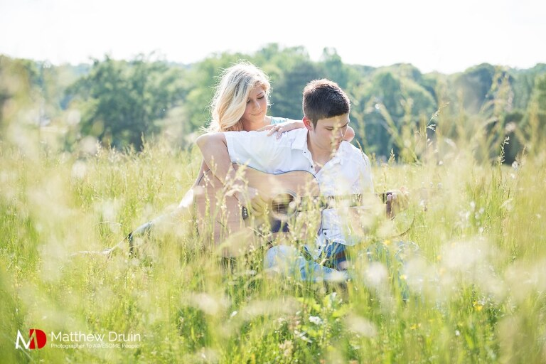 Girl sitting behind guy playing guitar in field at romantic sunset engagement