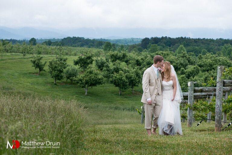 Bride and groom walking through vineyard after hiring wedding planner