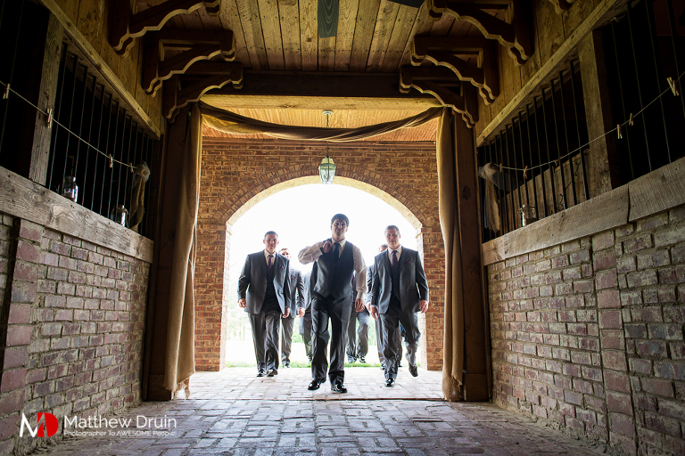 Groom walking through horse barn with groomsmen at wedding venue The Farm in Rome Georgia Review