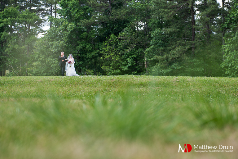 Bride walking with father through field to ceremony at wedding venue The Farm in Rome Georgia Review