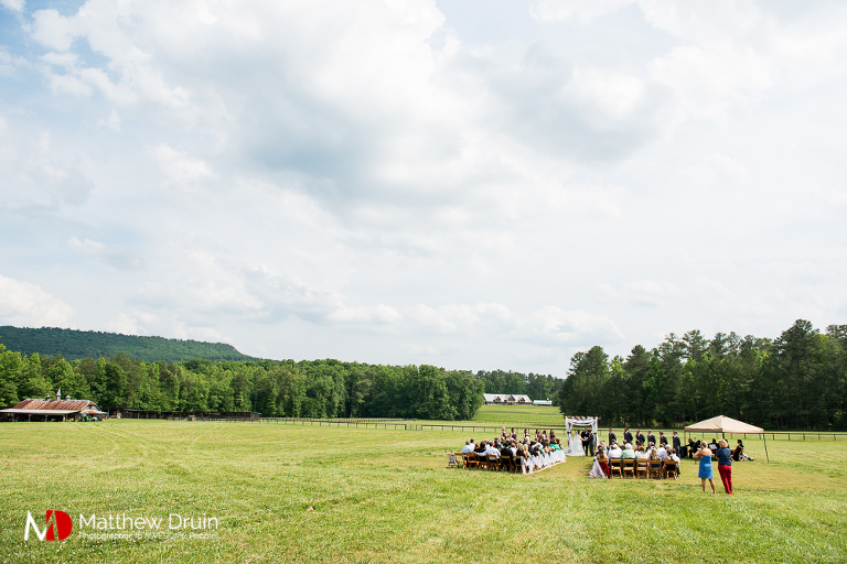 Wide shot of wedding ceremony in the middle of a field at wedding venue The Farm in Rome Georgia Review