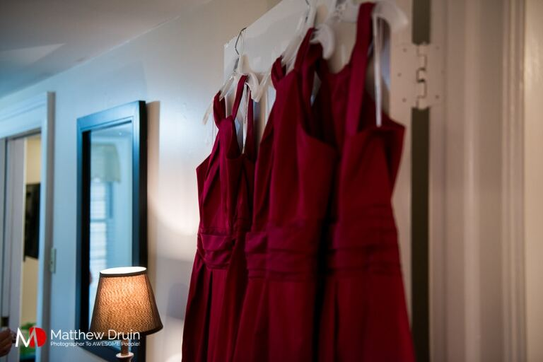 Red bridesmaid dresses hanging on door at Forsyth Park Savannah wedding