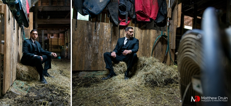 Groom sitting on bails of hay in barn in the Blue Ridge Mountains