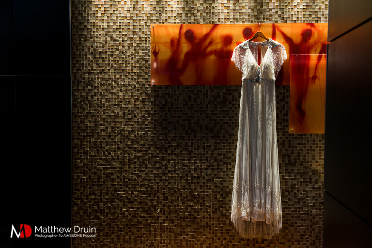 Bride's wedding dress hanging on orange wall artwork at The Peachtree Club wedding