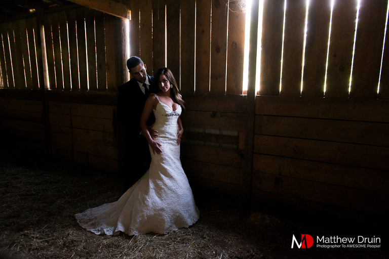 Bride and groom standing in barn with sunset light filtering through in the Blue Ridge Mountains