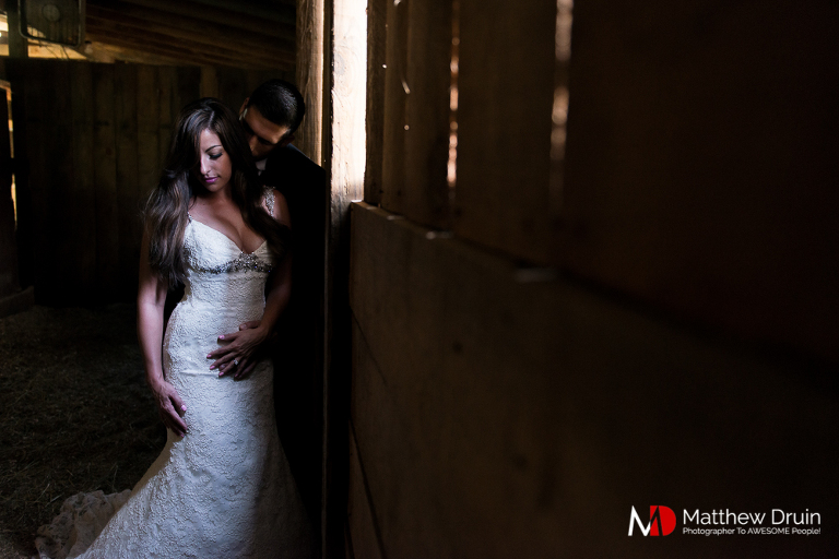 Groom hugging bride from behind in light-filled barn in the Blue Ridge Mountains