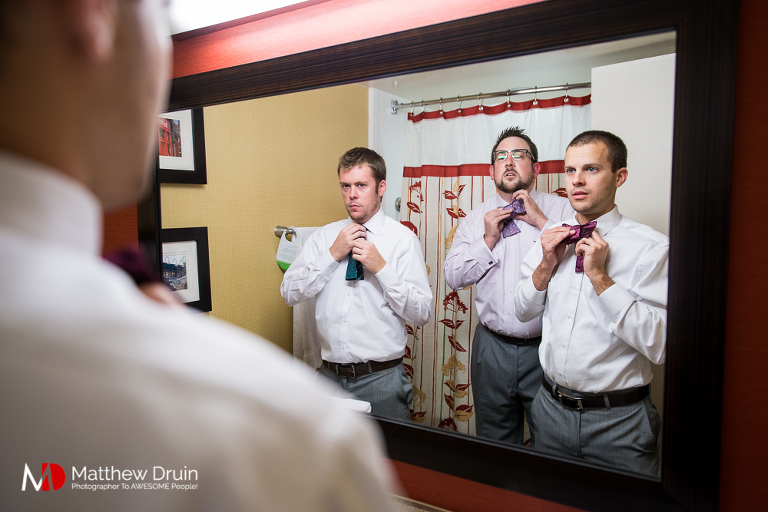 Groom putting on bowtie in mirror for Dekalb Courthouse wedding