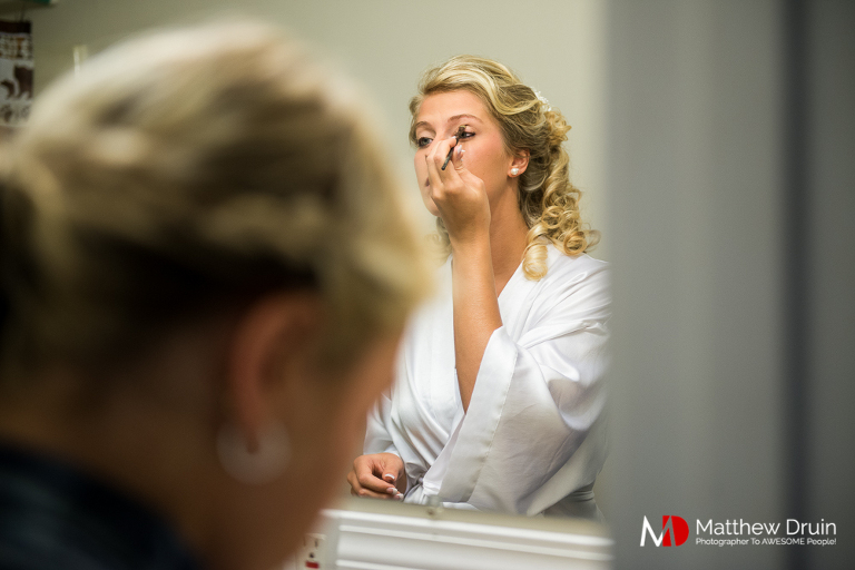 Bride doing her makeup in bathroom mirror for country Georgia wedding in Woodstock