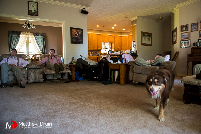 Groomsmen sitting in living room with dog at country Georgia wedding in Woodstock
