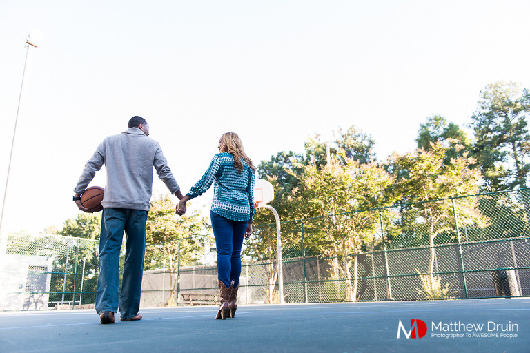 Engaged couple holding hands on basketball court at basketball themed Atlanta engagement session