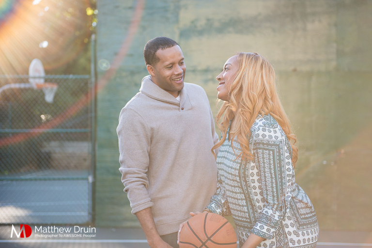 Guy trying to get basketball from girl with sunflare at Basketball Themed Atlanta Engagement Session