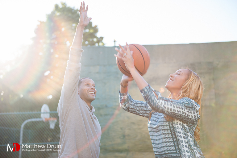 Guy trying to block girl from shooting basketball at Basketball Themed Atlanta Engagement Session