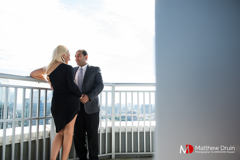 Engaged couple standing on high-rise balcony at Buckhead Atlanta Engagement Session