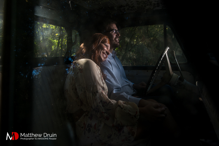 Girl leaning against guy sitting in old farm truck at Georgia engagement session