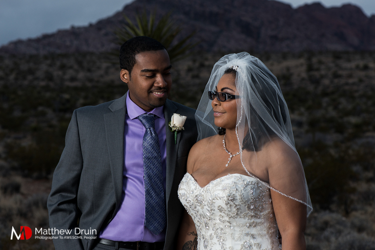 Bride and groom looking at each other in Las Vegas desert with storm clouds