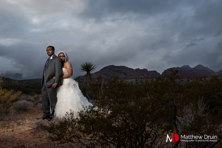 Bride holding groom from behind in Las Vegas desert with storm clouds