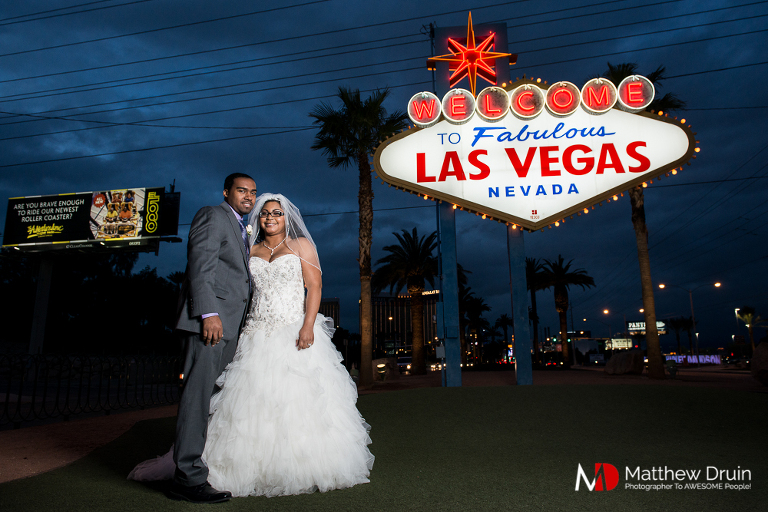 Bride holding groom from standing in front of famous Las Vegas sign