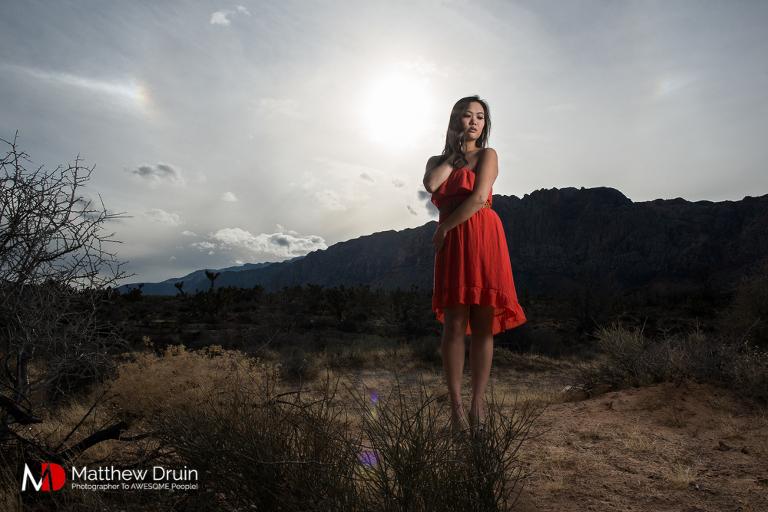 Girl standing in Las Vegas desert in red dress at sunset