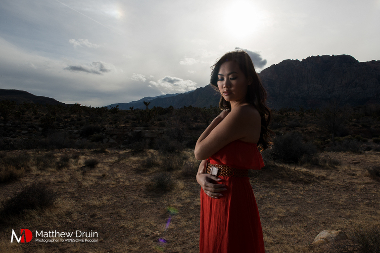 Girl standing in Las Vegas desert holding herself in red dress at sunset