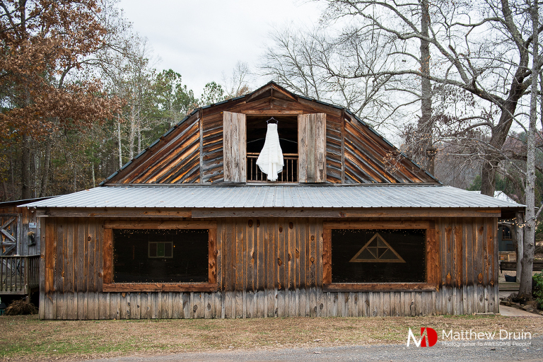 Bride's wedding dress hanging in barn window at Atlanta Wedding Venue Proctor Farm In Georgia Review