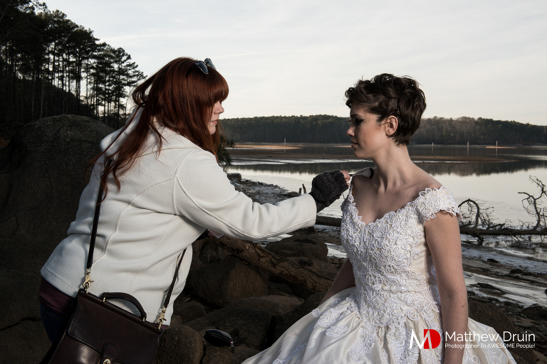 Makeup artist applying makeup on bride in empty lake in Acworth Georgia