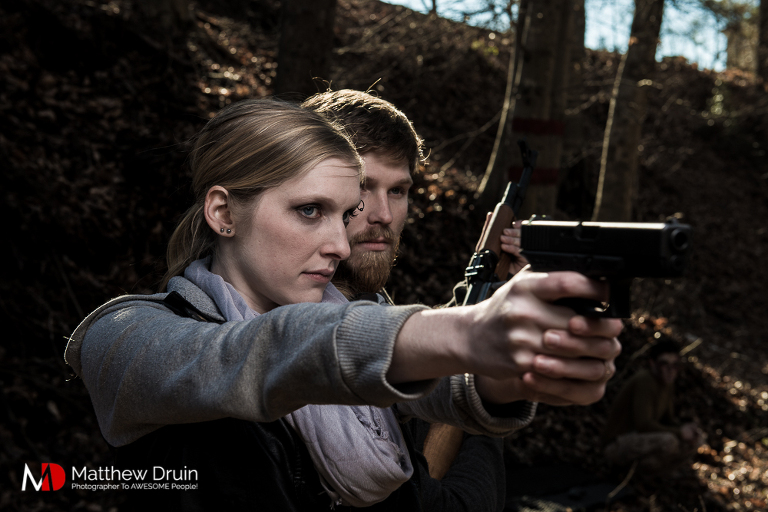 Engaged couple aiming gun in Georgia woods for the Walking Dead engagement session