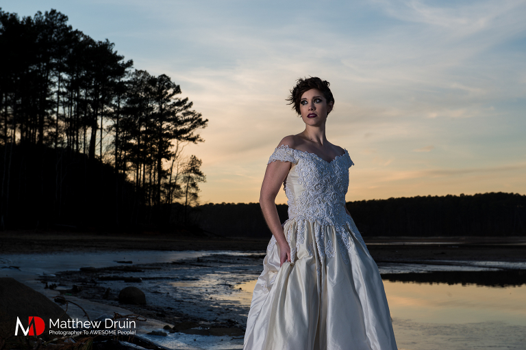 Bride standing in frozen lake in Atlanta at sunset