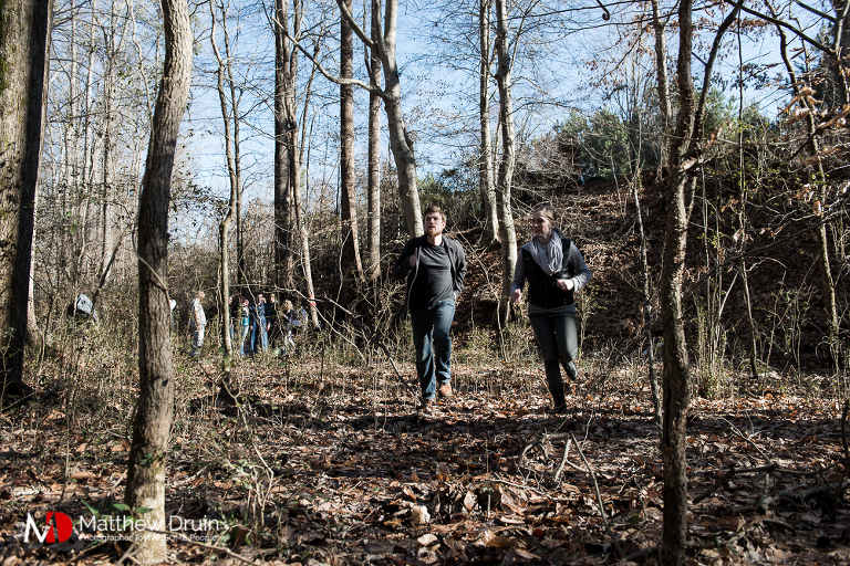 Engaged couple running from zombies in Atlanta woods for the Walking Dead engagement session