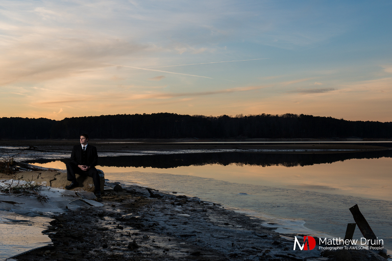 Groom sitting in frozen lake in Atlanta at sunset