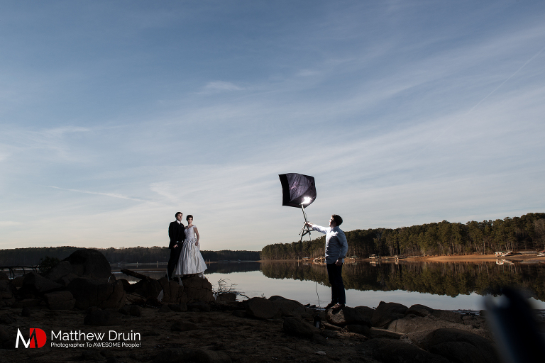 Behind the scenes of photo assistant holding a light on bride and groom Groom standing in frozen lake in Atlanta at sunset