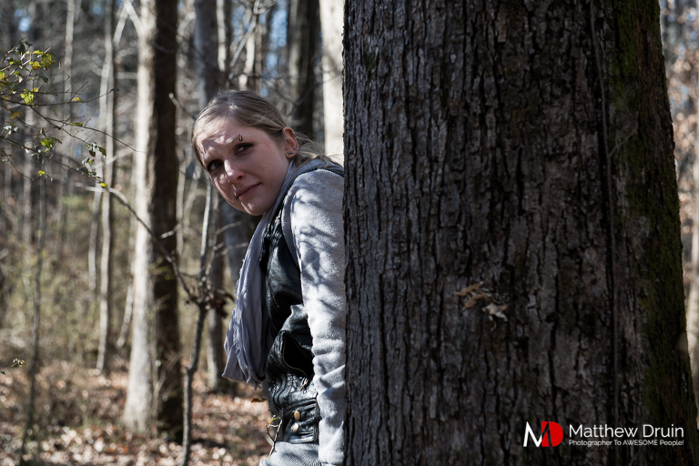 Girl looking around tree at zombies in Atlanta woods for the Walking Dead engagement session
