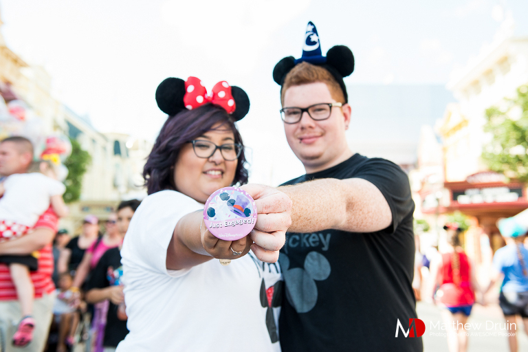 Couple holding Just Engaged Disney button at Walt Disney World engagement session from Atlanta wedding photographers Matthew Druin + Co.