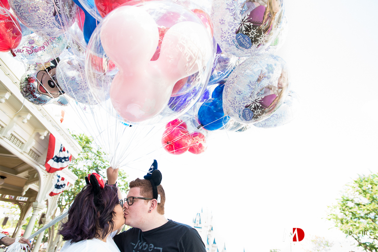 Engaged couple holding Disney balloons at Walt Disney World engagement session from Atlanta wedding photographers Matthew Druin + Co.