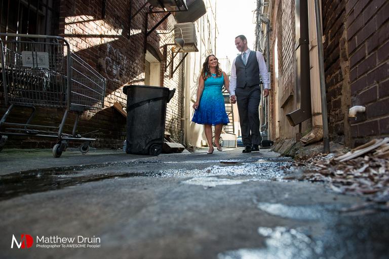 Engaged couple walking through alley at Atlanta engagement session from Atlanta wedding photographers Matthew Druin + Co.