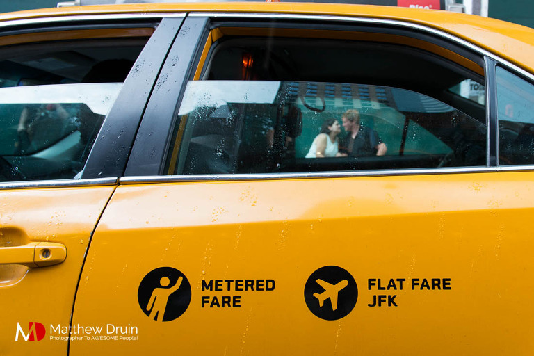 Engaged couple in Times Square through taxi cab window in New York City engagement session from Atlanta wedding and portrait photographer Matt Druin.