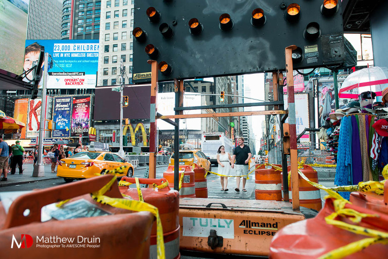 Engaged couple in Times Square through construction in New York City engagement session from Atlanta wedding and portrait photographer Matt Druin.