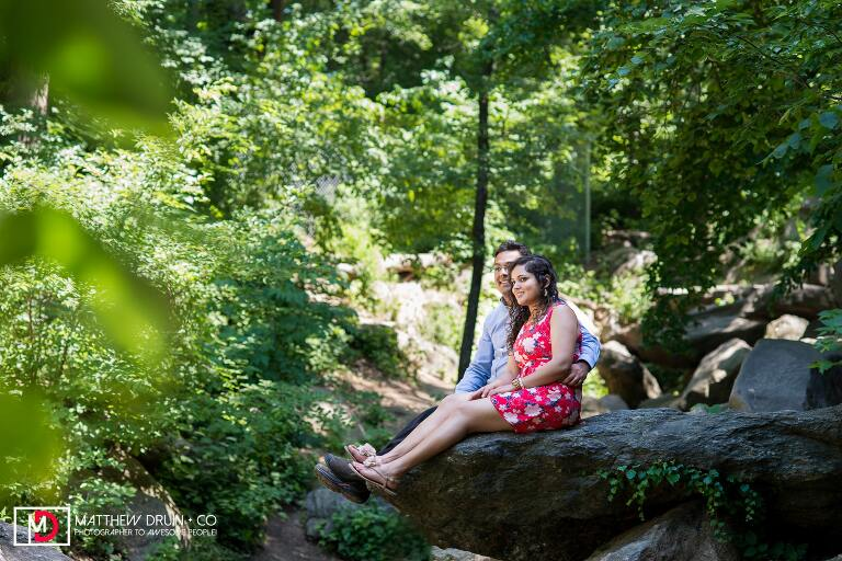Bride and groom sitting on waterfall rocks in Central Park during a New York City engagement