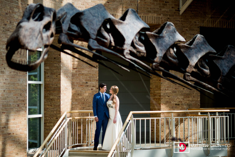 Bride and groom standing with dinosaur at Atlanta Fernbank Museum wedding