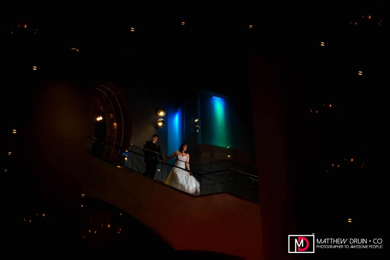 Bride and groom walking down W Hotel stairs at night after rainy Atlanta wedding at The Atrium