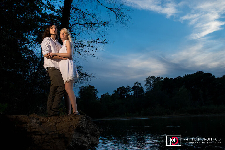 Engaged couple standing on rock cliff by river at sunset during their romantic Atlanta engagement session at Morgan Falls Park