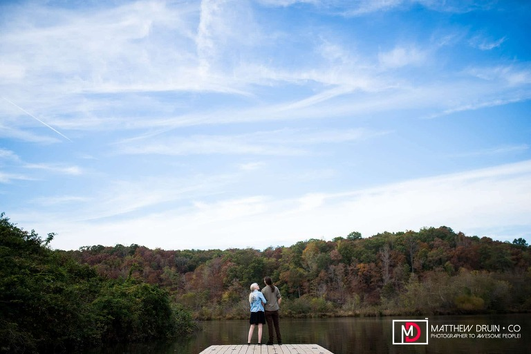 Engaged couple standing on river dock during their romantic Atlanta engagement session at Morgan Falls Park