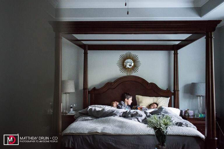 Kids jumping on bed waking up dad in the morning from Atlanta family documentary photographers