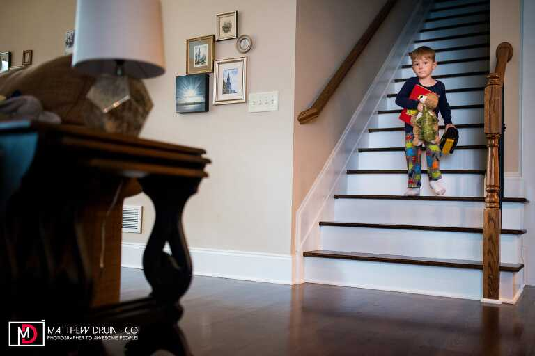 Kid walking downstairs with toys in the morning from Atlanta family documentary photographers