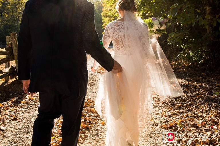 Bride and groom walking in sunset dirt road at farm wedding at Neverland Farms