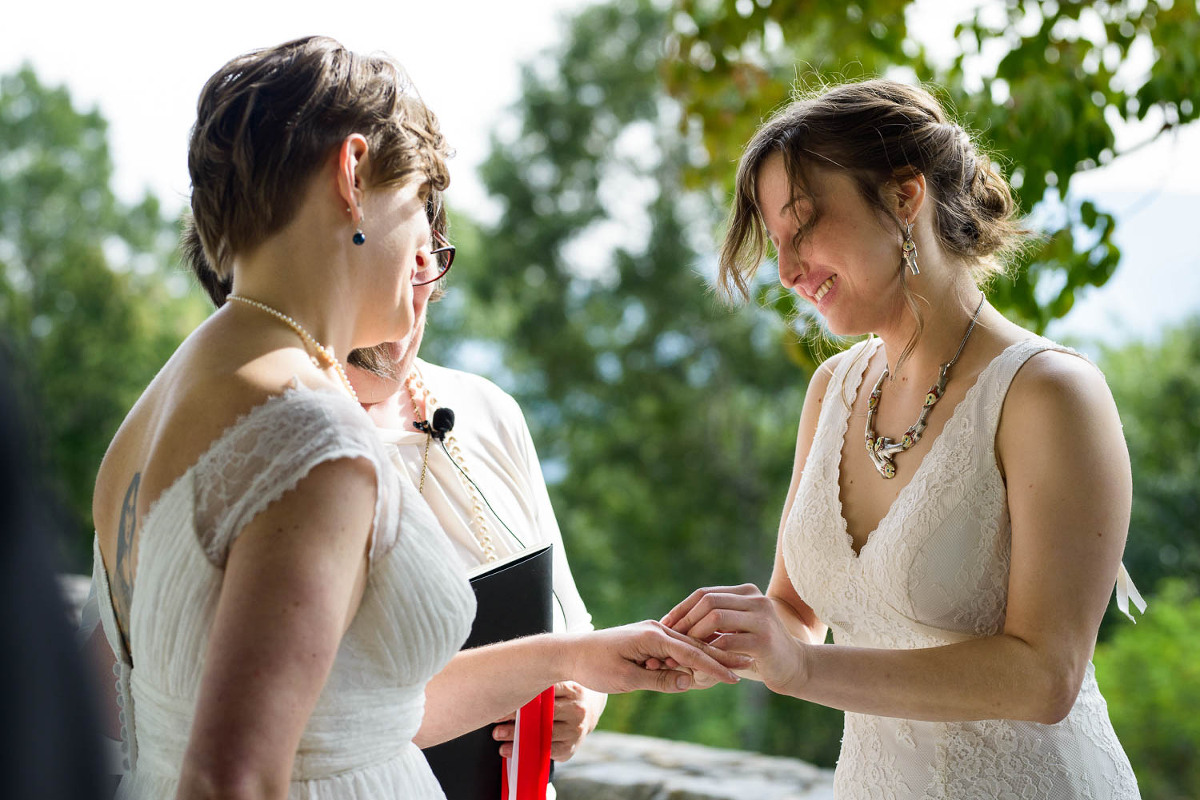 LGBT couple bride and bride exchanging rings during outdoor Atlanta wedding ceremony
